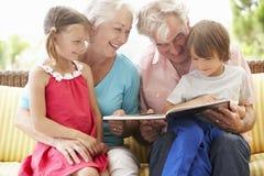 Morföräldrar och barnbarnläsebok på trädgårds- Seat Royaltyfria Bilder