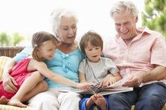 Morföräldrar och barnbarnläsebok på trädgårds- Seat Arkivfoto