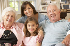 Morföräldrar som sitter på Sofa With Grandchildren Indoors Arkivfoto