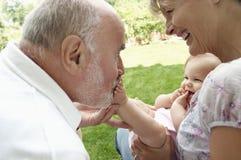 Morföräldrar som spelar med sondottern Arkivbilder