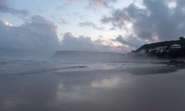 Morgan Bay beach at dusk, Wild Coast, Eastern Cape, South Africa. The clouds are reflected in the water on the beach. Morgan Bay beach at sunset, on the Wild stock photography