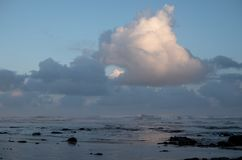 Morgan Bay beach at sundown, Wild Coast, Eastern Cape, South Africa. The clouds are reflected in the water on the beach. Morgan Bay beach at sundown, on the stock photography