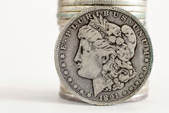 1891 Morgan Dollar. Coin stands against a stack of coins Royalty Free Stock Images