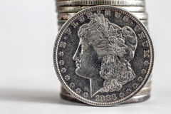 1883 Morgan Dollar. Coin stands against a stack of coins Royalty Free Stock Photography