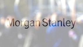 Morgan Stanley Inc. logo on a glass against blurred crowd on the steet. Editorial 3D rendering. Morgan Stanley Inc. logo on a glass against blurred crowd on the stock video footage