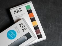 Box holding JUUL nicotine dispenser and pods stock photos