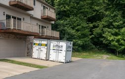 UPack moving containers on drive of townhouse Stock Photography