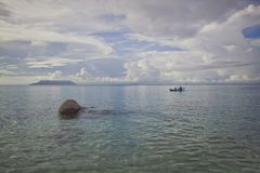 Morgen auf dem Ozean Einsames Boot mit Ruderern im Hintergrund Die Leute im Boot im Hintergrund sind unscharf stockbild