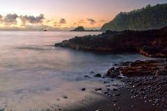 Morgen auf dem schwarzen Sandstrand von Hana Bay auf der Insel von Maui Stockfotografie