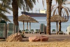 Morgen auf Elat-Öffentlichkeitsstrand Großes Frachtschiff auf Horizont Stockbild
