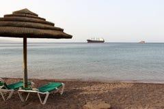 Morgen auf Elat-Öffentlichkeitsstrand Großes Frachtschiff auf Horizont Isra Lizenzfreies Stockbild
