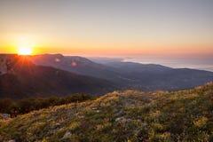 Morgen Dawn Sunlight des hellen goldenen Sonnenaufgangs mit gelbe Blumen-grünen Hügeln und buntem Himmel stockfotografie