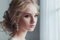 Morgen der Braut Schöne junge Frau in der eleganten weißen Robe mit der Modehochzeitsfrisur, die nahe steht Stockbilder
