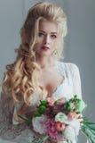 Morgen der Braut Schöne junge Frau im weißen Negligé, das nahe dem Fenster mit einem Blumenstrauß bleibt Stockfotos