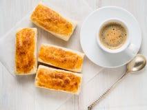 Morgen-Frühstück mit neuen Rollen des Blätterteiges und des Tasse Kaffees auf weißem Holztisch Stockbilder