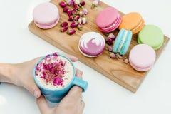 Morgen französische macarons auf hölzernem Schreibtisch auf Frau übergibt das Halten der Schale Cappuccinos Lizenzfreie Stockfotos