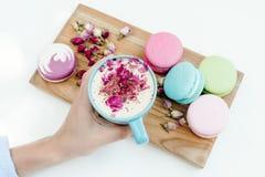 Morgen französische macarons auf hölzernem Schreibtisch auf Frau übergibt das Halten der Schale Cappuccinos mit den Rosenblumenbl Stockfotografie