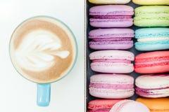 Morgen frische französische macaron Plätzchen und blaue Schale Cappuccino auf weißer Tabelle Lizenzfreie Stockfotos
