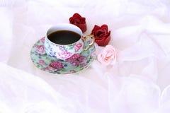 Morgen heißes coffe im Becher und in den wenig roten und rosa Blumen auf weißem Satinhintergrund Nahaufnahme, Draufsicht Saisonal Lizenzfreie Stockfotografie