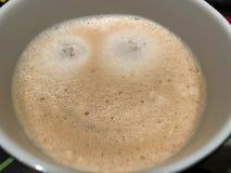 Morgen-Kaffeecappuccino Latte mit lächelndem willkommenem glücklichem Gesicht des Schaums oder der Schokolade haben einen schönen Stockfotografie