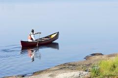 Morgen-Paddel in einem roten Kanu Stockfotografie