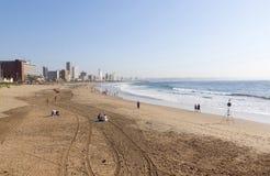 Morgen-Reifenbahnen und -leute auf Strand in Durban Lizenzfreie Stockfotografie
