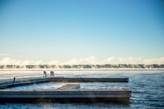Morgen-Sonnenaufgang auf einem Dock mit Stühlen und Nebel Muskoka Lizenzfreies Stockfoto