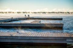 Morgen-Sonnenaufgang auf einem Dock mit Stühlen und Nebel Muskoka Stockfotografie