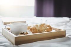 Morgen-Tasse Kaffee und Hörnchen auf dem Bett mit altem Buch stockbild
