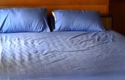 Morgenansicht eines ungemachten Betts mit zerknitterten blauen Bettwäschen Stockfoto