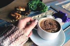 Morgencappuccino mit Herzen, mit Plätzchen und Blumen Lizenzfreies Stockfoto