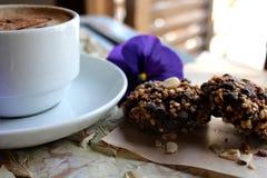 Morgencappuccino mit Herzen, mit Plätzchen und Blumen Stockfoto