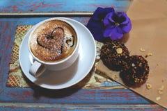 Morgencappuccino mit Herzen, mit Plätzchen und Blumen Stockbilder