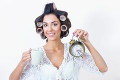 Morgeneile der jungen Frau mit Kaffee-, Uhr- und Haarlockenwicklern Stockfoto