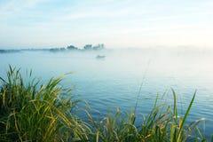 Morgenfischen auf einem nebelhaften See stockfotografie