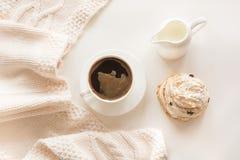 Morgenfrühstück, eine Schale schwarzer Kaffee mit Milch und Gebäck in den Pastellfarben mit warmem leichtem Schal auf einem Weiß  Stockfotos