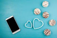 Morgenfrühstück für Valentinsgrußtag Smartphone, Pralinen, zwei dekorative Herzen auf blauem Hintergrund Draufsicht, flache Lage lizenzfreie stockfotos