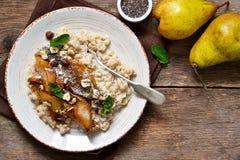Morgenfrühstück Hafermehl, karamellisierte Birne und gebratene Haselnüsse stockfotografie