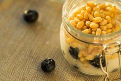 Morgenfrühstück mit Kiefernnüssen, Blaubeeren und Jogurtnahaufnahme Stockfoto
