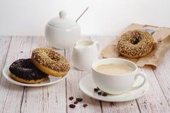 Morgenfrühstück mit Schokoladenschaumgummiringen und -Tasse Kaffee mit Sahne auf hellem hölzernem Hintergrund Köstliche Schaumgum stockbilder
