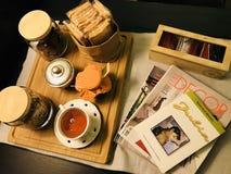Morgenfrühstück mit Tee, Plätzchen und Zeitschriften stockfoto