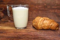 Morgenfrühstück von Milch und von Hörnchen auf einem Holztisch Stockfotografie
