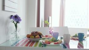 MorgenFrühstückstisch mit Blumenstrauß der Blume und der Platte mit Frucht in der Wohnungsküche Langsame Bewegung 3840x2160 stock video
