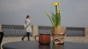 Morgenkaffee auf dem Tisch mit einem Blumenstrauß von Narzissen in einem offenen Café Leute leiten einen unscharfen Hintergrund w stock video footage