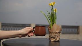 Morgenkaffee auf dem Tisch mit einem Blumenstrau? von Narzissen in einem offenen Caf? Leute leiten einen unscharfen Hintergrund w stock video footage
