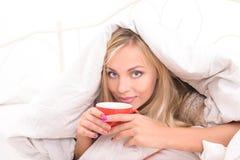 Morgenkaffee für blondes Mädchen im Bett Stockfotografie