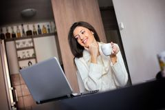 Morgenkaffee vor einem Laptop Stockfotos