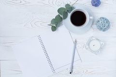 MorgenKaffeetasse für Frühstück, leeres Notizbuch, Bleistift und Blumen auf weiße Tischplatte Frauenarbeitsschreibtisch Lizenzfreies Stockbild
