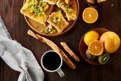 Morgenkonzept mit einem Tasse Kaffee, Breadsticks, Fruchttorten und Orangen auf hölzernem Hintergrund Lizenzfreies Stockbild