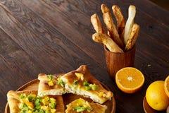 Morgenkonzept mit einem Tasse Kaffee, Breadsticks, Fruchttorten und Orangen auf hölzernem Hintergrund Stockfotos